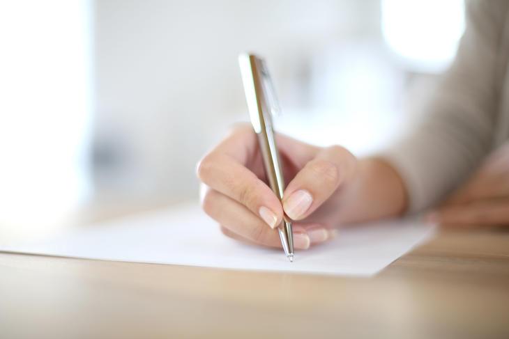Kvinne skriver under på papir